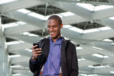 smiling black businessman smiling and looking at mobile phone