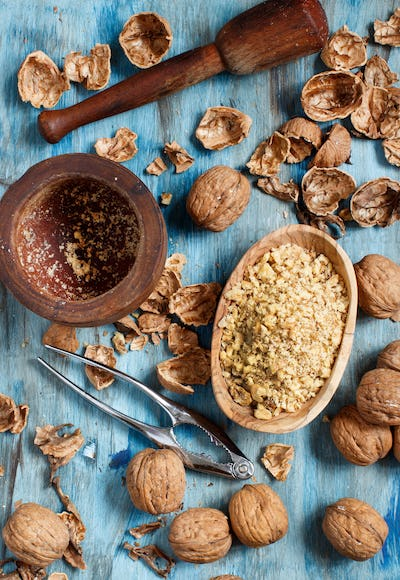 Fresh walnuts and mortar on a blue wooden table