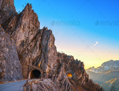 Alpi Apuane mountain road pass and double tunnel view at sunset.