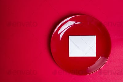 red plate with a piece of white paper