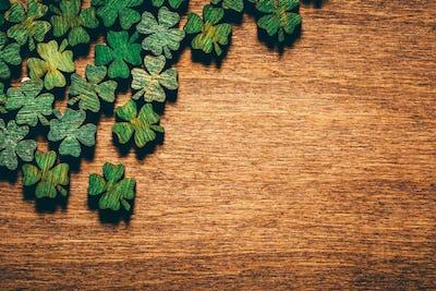 Green wooden four leaf shamrocks on wooden board
