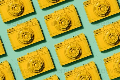 Retro yellow cameras on green background