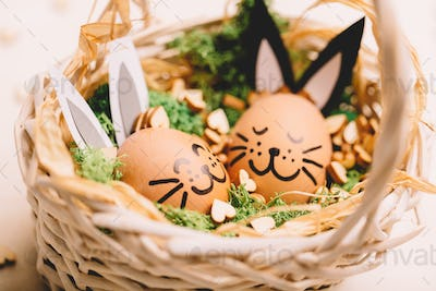 Two smiling egg-bunnies laying in the basket.