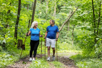 Elderly couple enjoying summer walk in the forest.