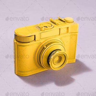 Yellow camera on pastel background.