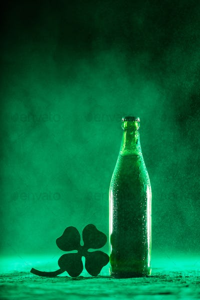 Beer bottle and a shamrock on a dusty background