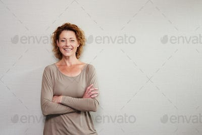 Older woman smiling with arms crossed by wall