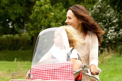 Mother and daughter riding on bicycle in the park