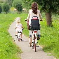 Mother and daughter riding bicycles in park