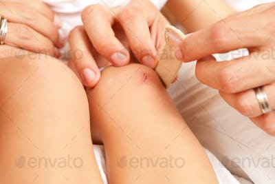 Mother puts bandage on the knee of her daughter
