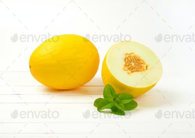 one and half yellow melons on white wooden background