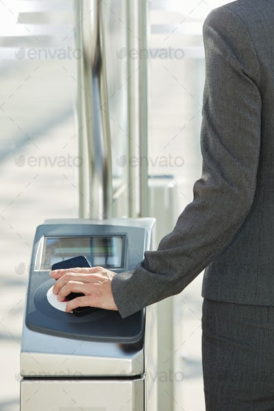 Woman walking through turnstile with pass