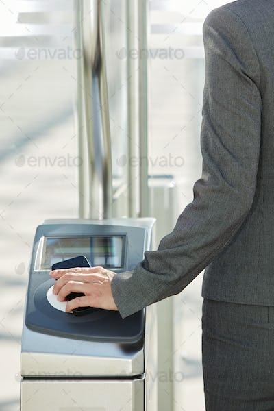Woman walking through turnstile with pass