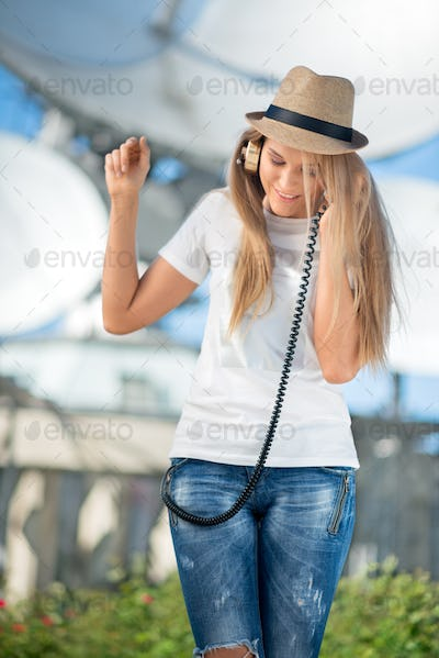 Happy young woman in hat listening to the music in vintage music