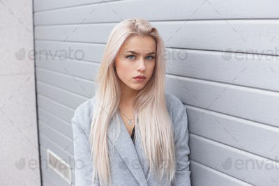 Beautiful young woman in a light coat near a white wall