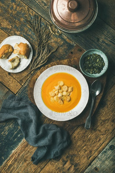 Warming pumpkin cream soup with croutons and seeds, vertical composition