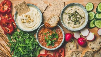 Flat-lay of Vegetarian dips hummus, babaganush, muhammara