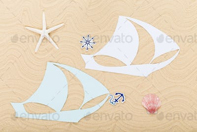 Paper clipper boats on waved sand.