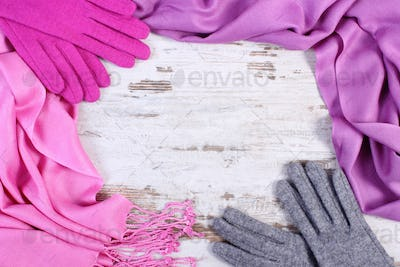 Frame of woolen gloves and shawl for winter, copy space for text on old rustic board