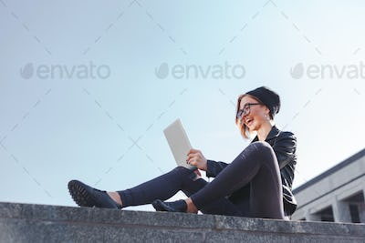 A young trendy hipster woman is laughing looking into her new electronic tablet outdoor.