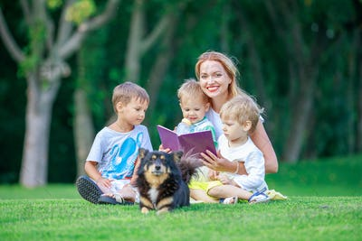 Young mother reading book to her two small sons