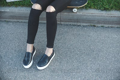 Young woman in jeans, sneakers sitting on the ground next to her skateboard outdoors