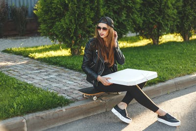 Young hipster woman with skateboard has a lunch with pizza box sitting outdoor