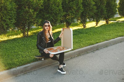 Young hipster woman with skateboard has a lunch with slice of pizza sitting outdoor