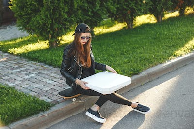 young woman - teenager with skateboard have a rest and eating pizza takeaway outdoor in street
