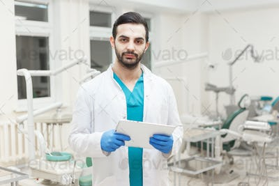 Portrait of young modern doctor with electronic tablet