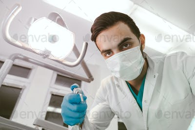 Portrait of a young doctor dentist at work. View from the first patient's face.