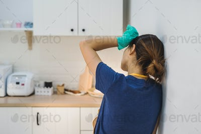 Tired young woman standing at kitchen room