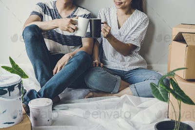Young happy couple moving in new home, sitting and relaxing on the floor