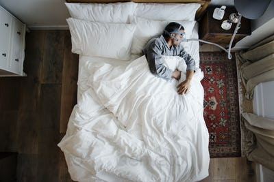 Man sleeping with an anti-snoring mask on