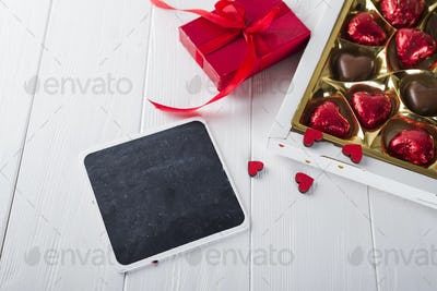 Delicious chocolate candies in gift box on white wooden background