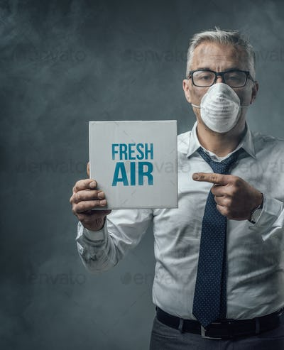 Businessman holding a sign and air pollution