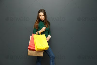 Female shopaholic holding colorful paper bags