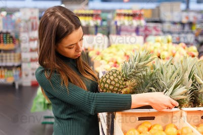Young brunette woman buying pineapple at grocery shop