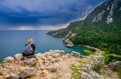 Female trekker resting on a cliff in Olympos