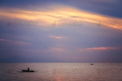 Small fisherman boat sailing at dusk