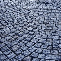 Street paving stone in blue tone. Antique urban sidewalk. Horizontal