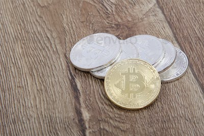 Silver bitcoins and one gold on a table