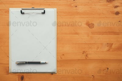 Overhead view of blank clipboard note pad paper with pen