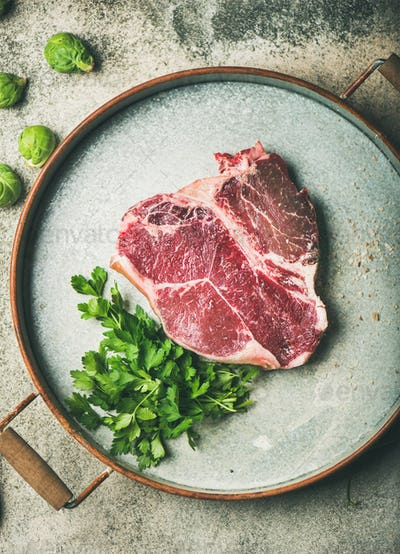 Flat-lay of raw uncooked dry-aged t-bone prime beef steak