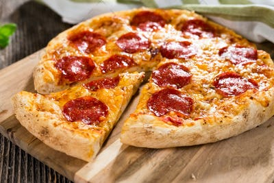 Pepperoni pizza on rustic background