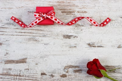 Wrapped gift with red ribbon and rose for Valentines Day, copy space for text on rustic board