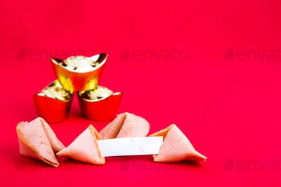 Fortune cookies with decorative gold nuggets on red background