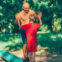 Grandfather and grandson  exercising in park