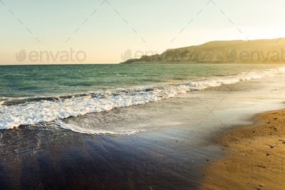 Sea waves and sandy beach at sunset. Toned and saturated image