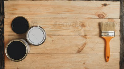 Two paint tins and brush on wooden background with copy space in center, top view